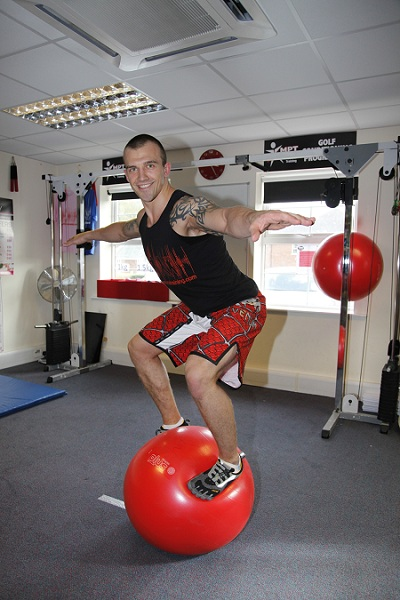 fitness trainer balancing on a stability ball