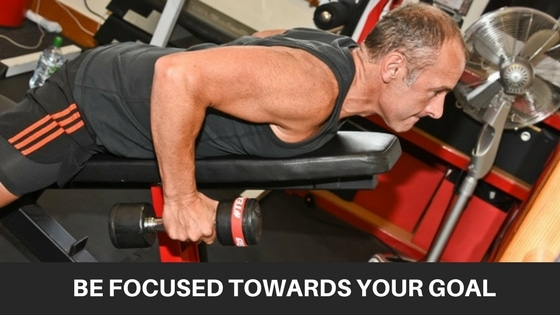 man doing a back exercise with dumbbells whilst led face down on an inclined exercise bench