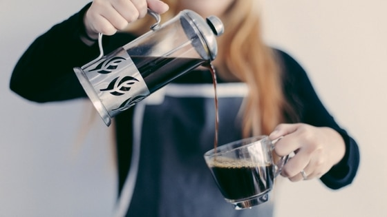 a woman pouring black coffee from a cafetiere to a cup