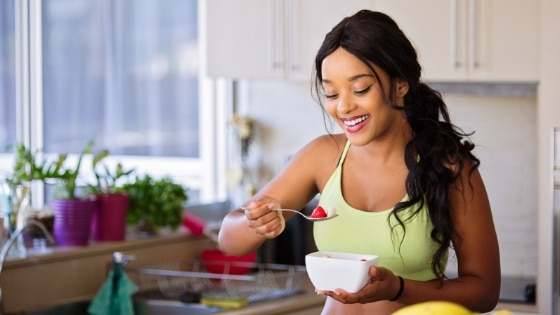 woman eating a healthy fruit bowl in a kitchen