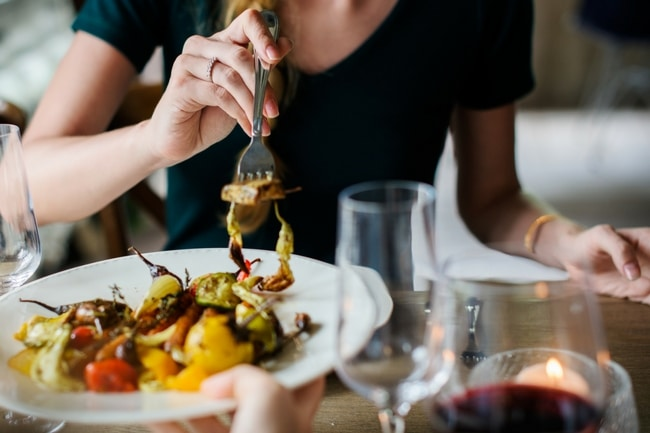 woman at the table eating some healthy food with a glass of red wine