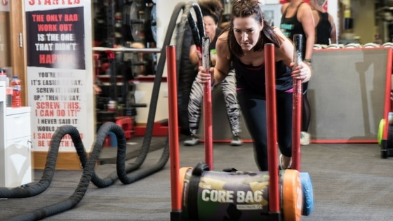 woman doing HIIT by pushing a sled filled with core bags