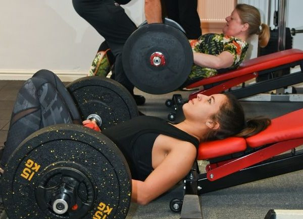 women doing glute extensions with barbells in a gym